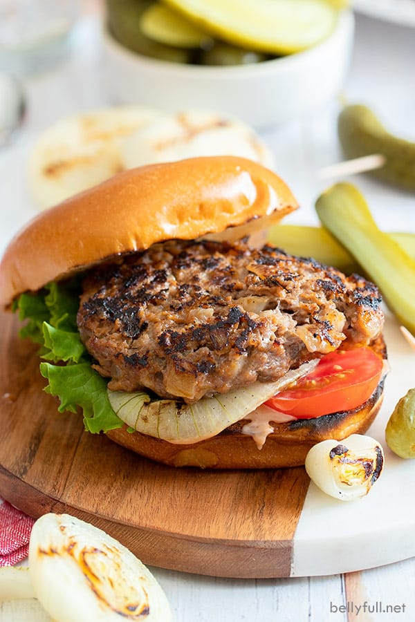 Onion burger on toasted bun with grilled onions, tomato, and lettuce