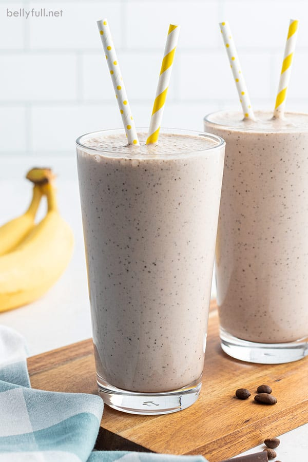 two tall glasses filled with banana smoothie and yellow striped straws