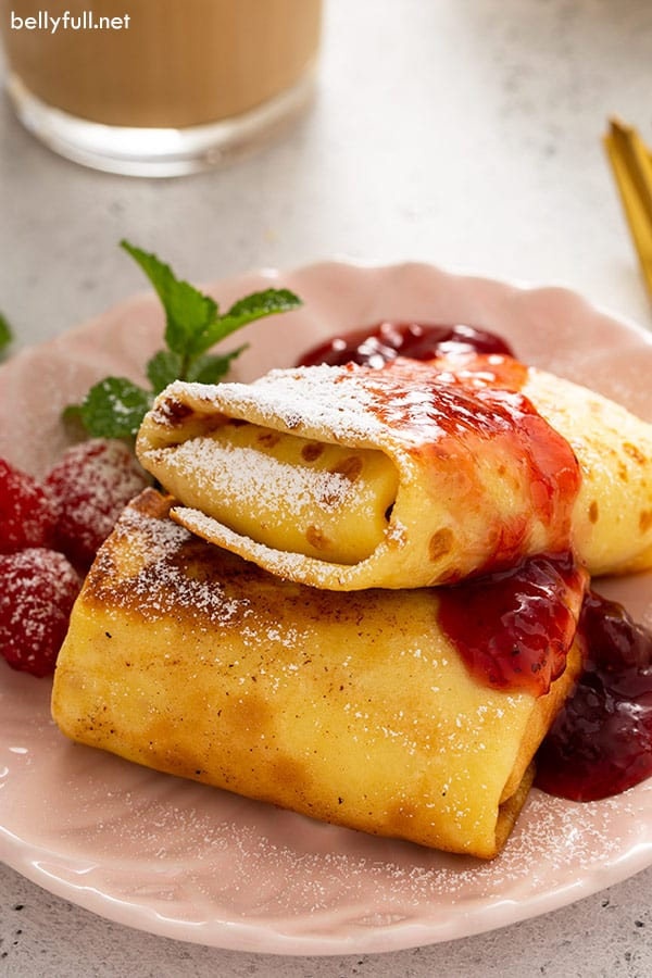 2 cheese blintzes on plate with strawberry jam and powdered sugar