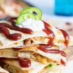 3 stacked quesadilla wedges with barbecue sauce and sour cream