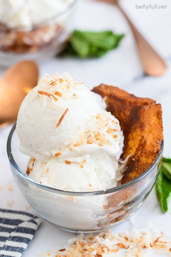 close up of glass dessert cup with 2 scoops of vanilla ice cream sprinkled with toasted coconut and a grilled pineapple ring