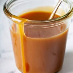 close up of caramel sauce in glass jar with spoon, running down side