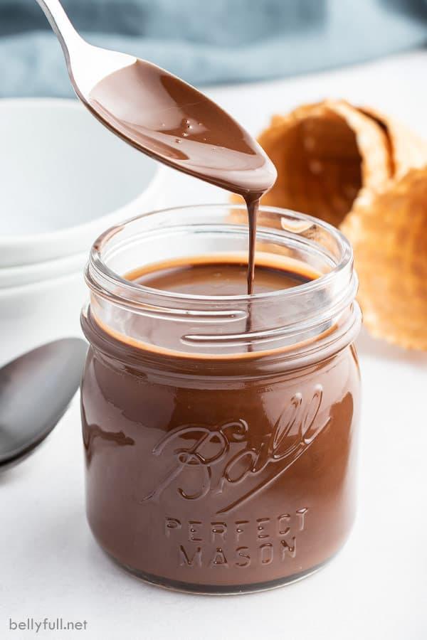 spoon drizzling homemade chocolate Magic Shell into glass jar