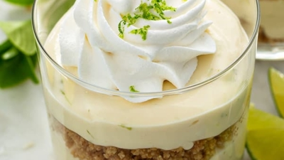 key lime cheesecake parfait in parfait glass with swirled whipped cream and lime zest