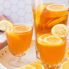 2 glasses and a pitcher filled with sweet tea and lemon slices on a white serving tray