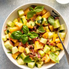 overhead Melon Cucumber Salad in white serving bowl with fresh basil leaves