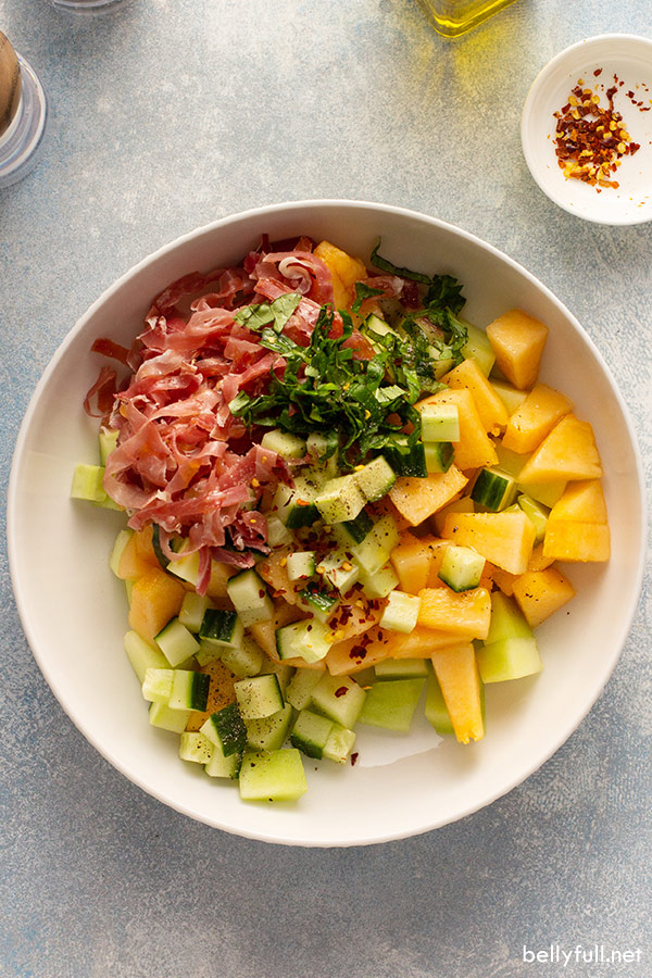 diced up honeydew, cantaloupe, cucumber, prosciutto, and basil in white serving bowl