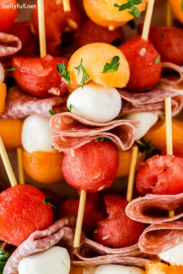 close up of mini fruit kabobs including watermelon, cantaloupe, fresh mozzarella, and salami,