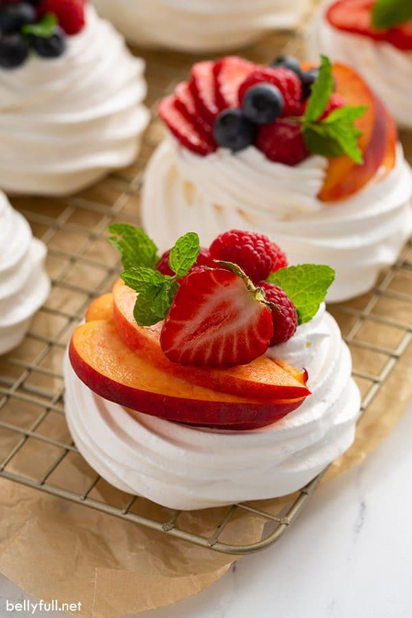 mini pavlova meringue with sliced fresh fruit on cooling rack