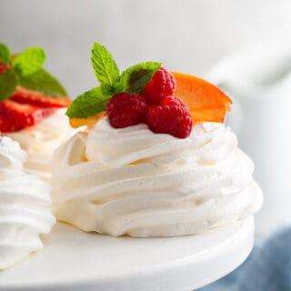 mini pavlova with fresh raspberries on white cake stand