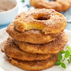 stack of 5 pineapple fritter rings with bite taken from top one