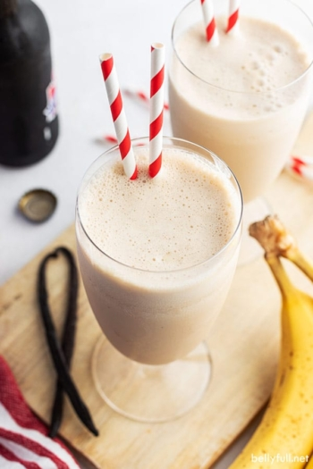 banana smoothie in glass with two straws