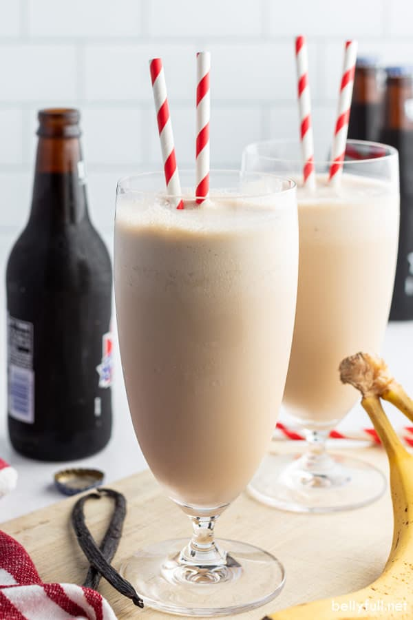 two tall glasses filled with banana smoothie and red striped straws with root beer bottle in the background
