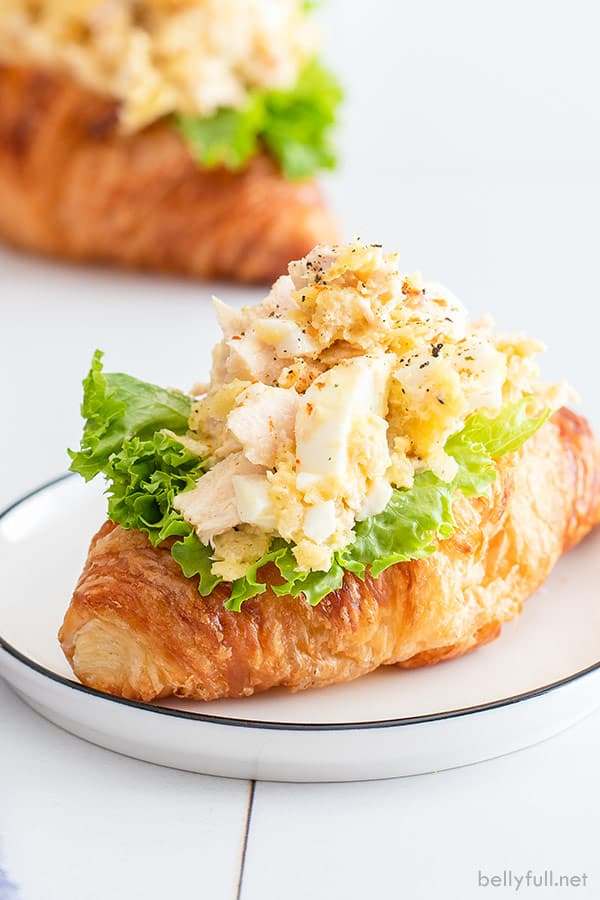 tuna salad with egg on a bed of lettuce on top of croissant