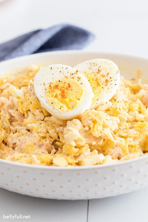 tuna salad with hard boiled egg halves in white serving bowl