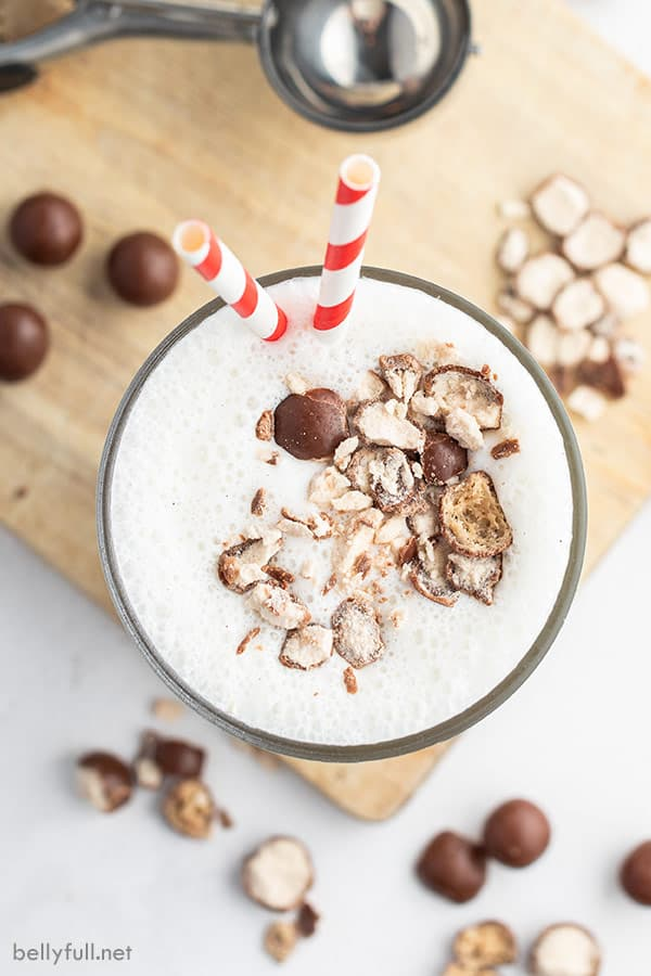 Overhead picture of vanilla malted milkshake in a tall glass with crushed up malted milk balls and a red white striped straw