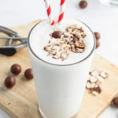 vanilla malted milkshake in a tall glass with crushed up malted milk balls and a red white striped straw