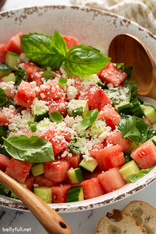 close up of salad with watermelon, cucumber, feta, and basil leaves in serving bowl