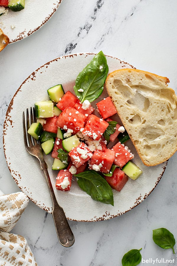 overhead of watermelon salad on ornate plate with slice of bread and fork