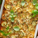 overhead of baked spiral zucchini rolls in white casserole dish