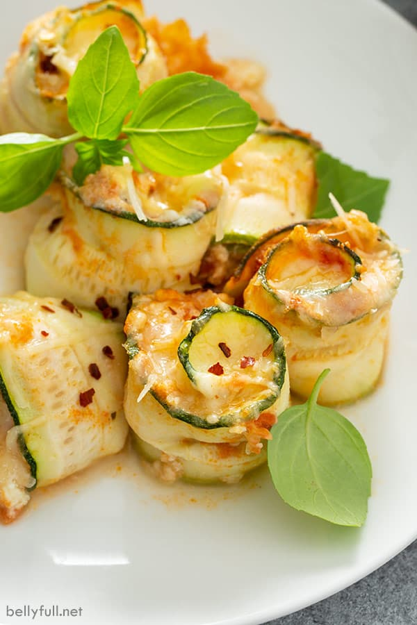 close up picture of baked zucchini lasagna rolls on white plate with basil leaves