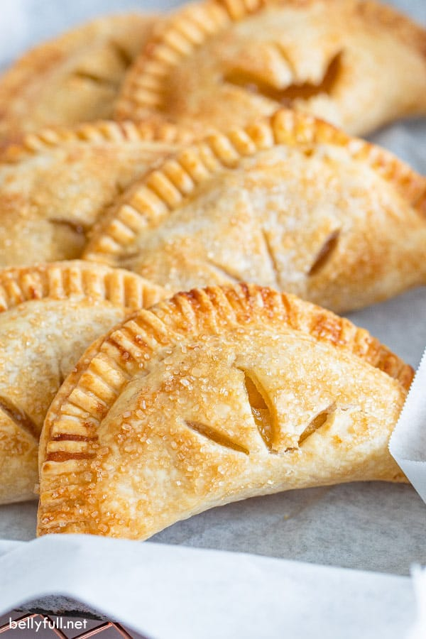 golden half moon shaped apple hand pies on parchment paper