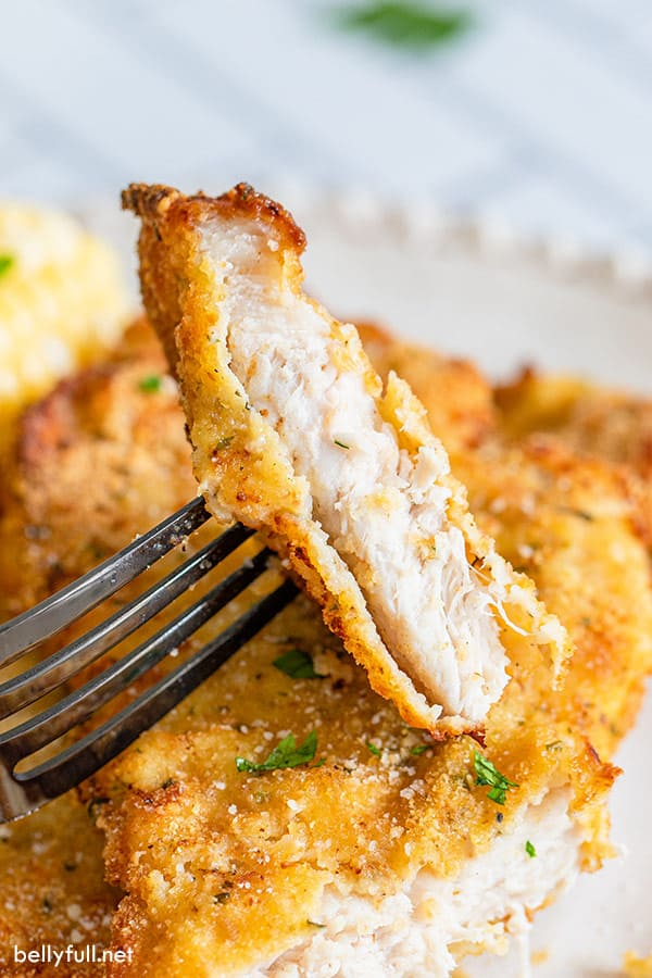 close up slice of cooked breaded pork chop on fork