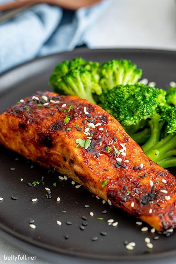 hoisin glazed air fried salmon on black plate with a side of broccoli