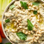 overhead of baba ganoush in dish with toasted pine nuts
