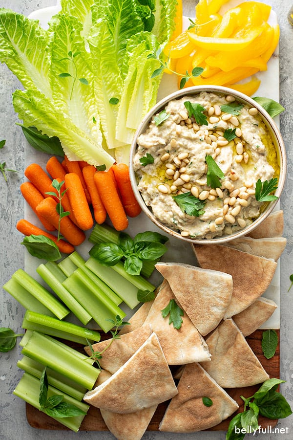 overhead of baba ganoush in white serving dish surrounded by carrots, celery, bell pepper, and pita wedges