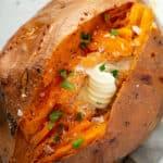 overhead of baked sweet potato split open with a dap of butter