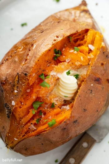 overhead of baked sweet potato split open with a dap of butter