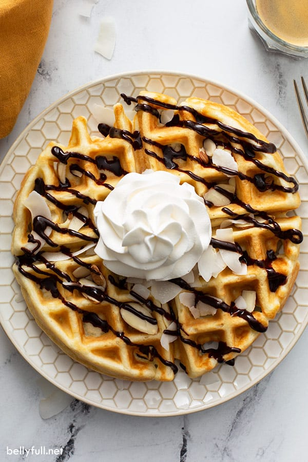 overhead of whole round waffle with coconut flakes, chocolate sauce, and whipped cream on plate