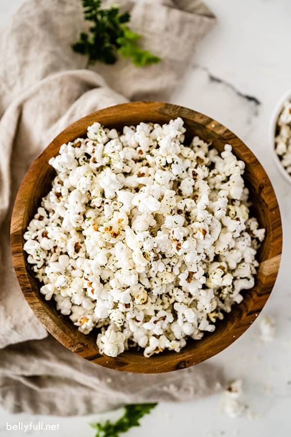 overhead of garlic bread popcorn in wooden bowl with brown napkin