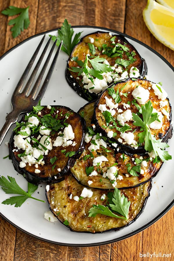 overhead of grilled eggplant with chopped fresh parsley and feta cheese on white plate