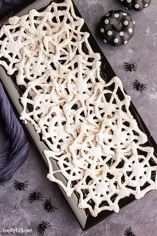 overhead of black serving tray filled with spiderweb halloween cookies