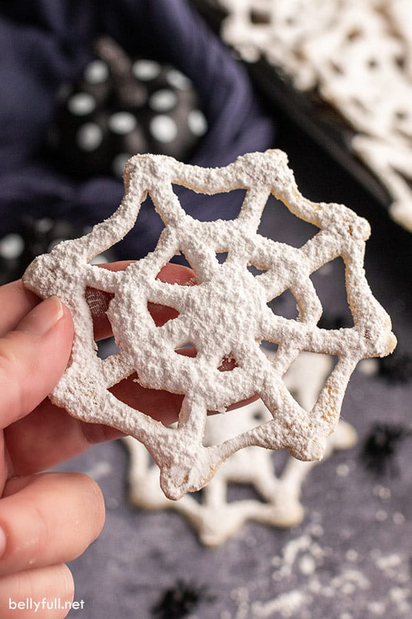close up of hand holding cobweb Halloween cookie