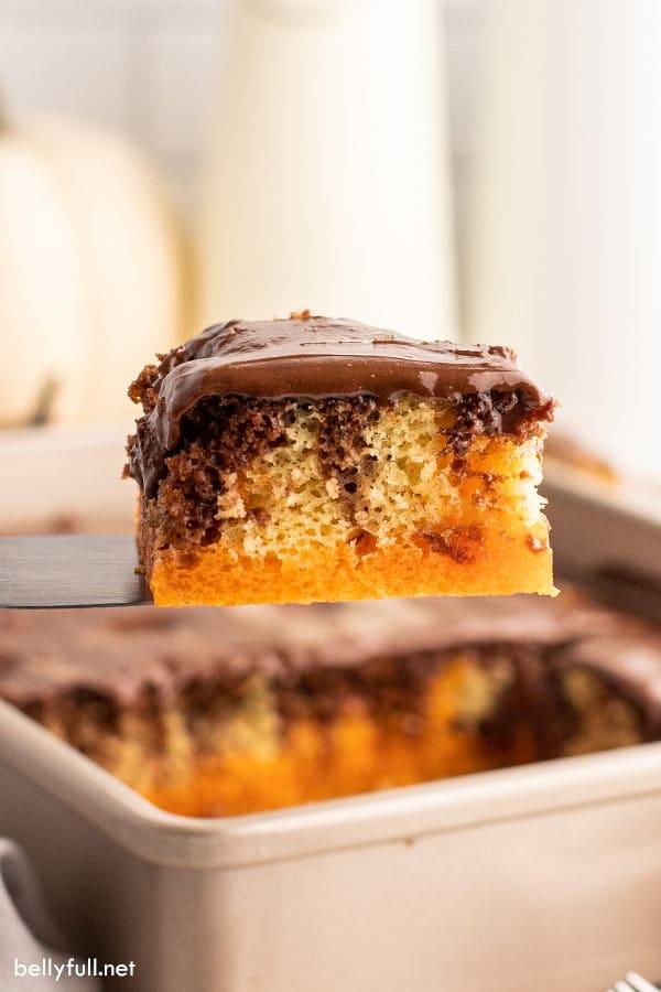 square slice of marble orange jello cake on metal spatula