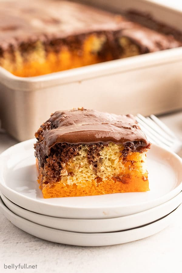 square slice of marble orange jello cake on stack of 3 white plates