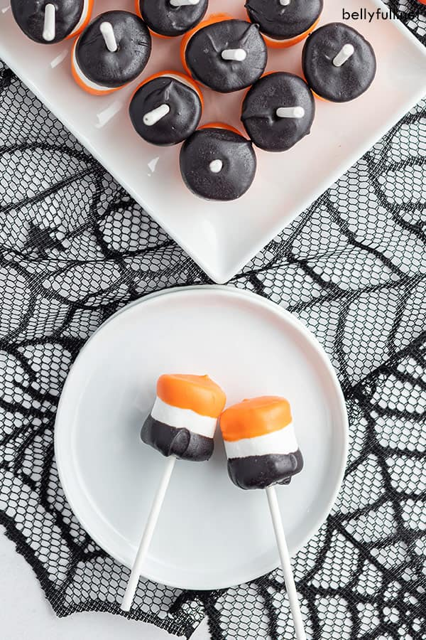 overhead of 2 Halloween Marshmallow Pops on white plate on top of black spiderweb tablecloth