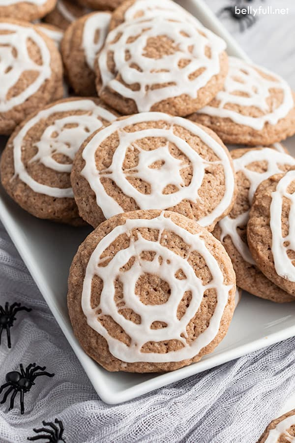 a white tray filled with chocolate sugar cookies with spiderweb icing