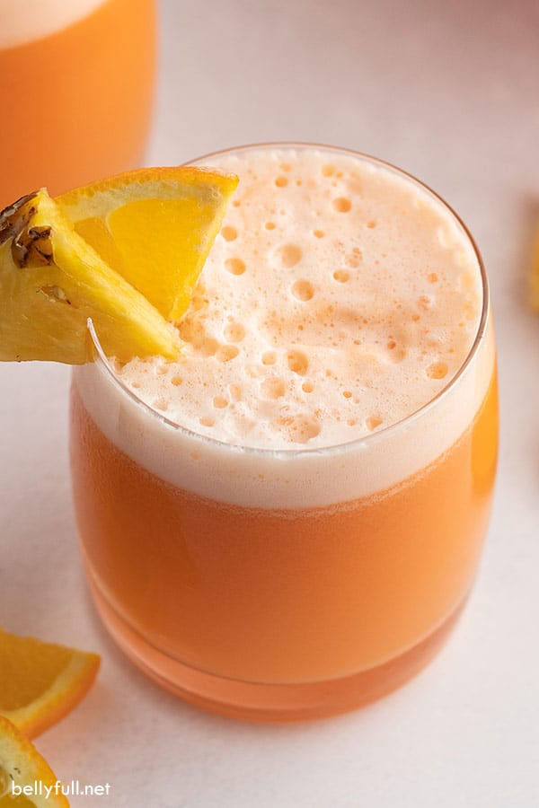 close up of glass tumbler filled with orange soda with pineapple wedge on rim
