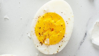 close up overhead of hard boiled egg sliced in half with shell to the side