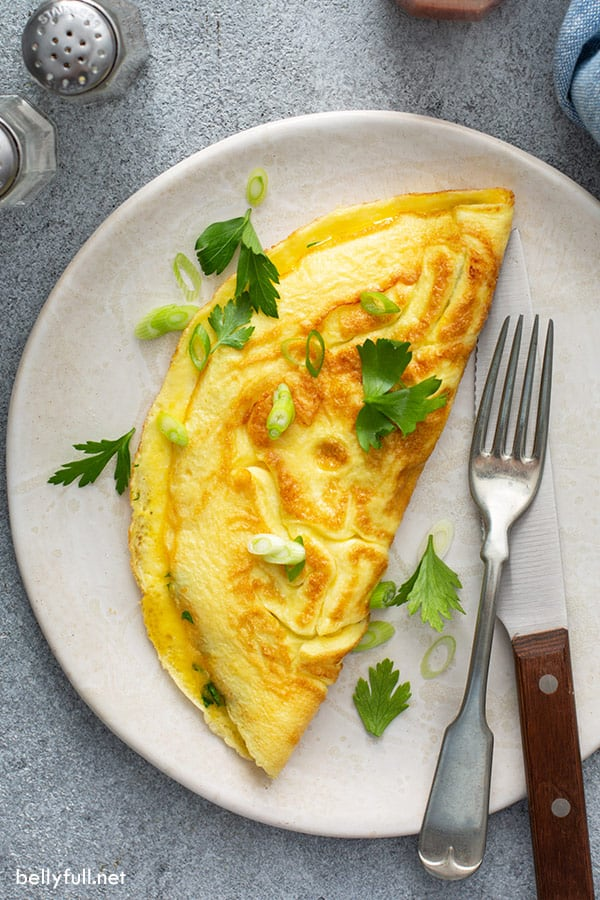 overhead picture of glistening omelette on plate with fresh herbs, fork and knife