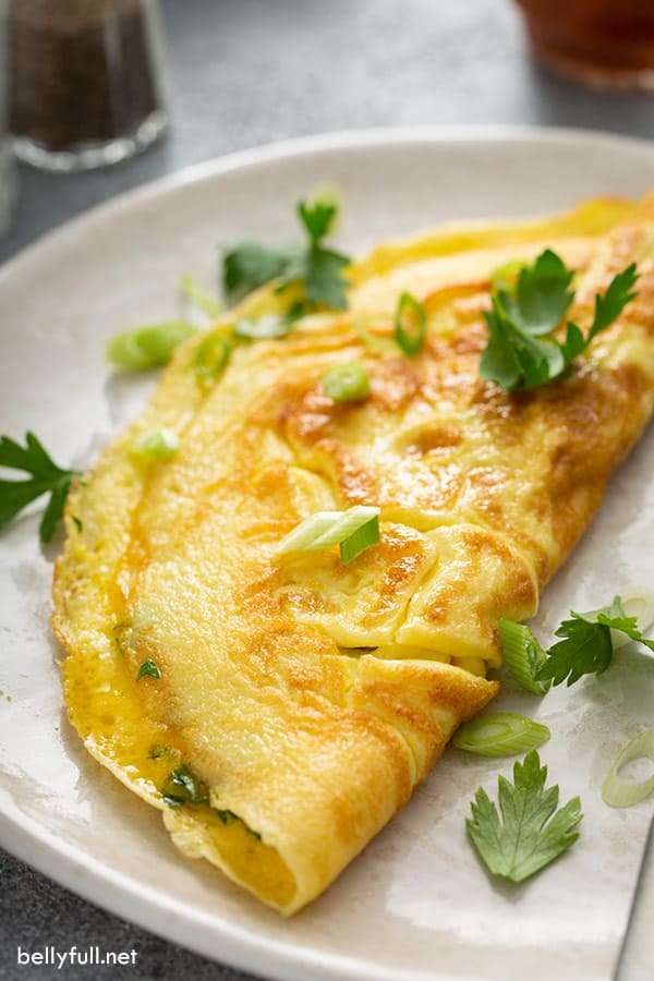 glistening omelette on white plate sprinkled with fresh chopped herbs