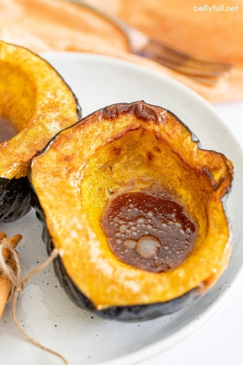 roasted acorn squash half with melted butter and brown sugar on plate