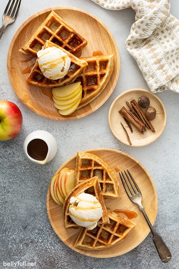 overhead of apple waffles on brown plates topped with vanilla ice cream and caramel sauce
