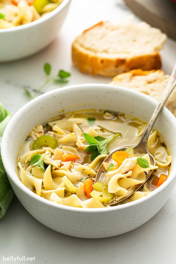 easy chicken noodle soup in speckled bowl with spoon and bread slices in background