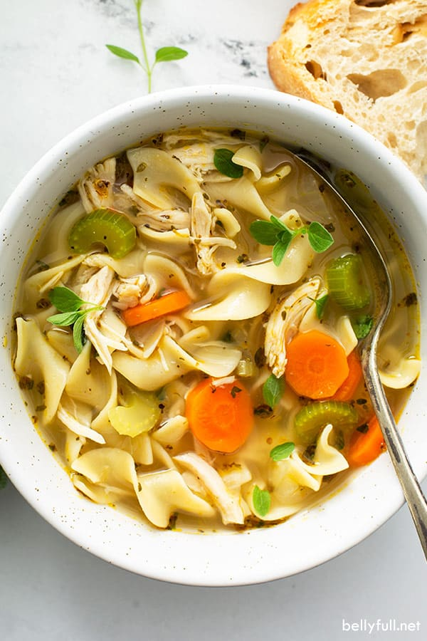 overhead of homemade chicken noodle soup in white bowl with spoon