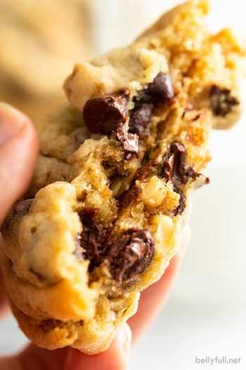 close up of gooey chocolate chip cookie broken in half